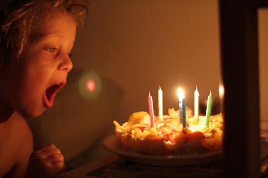 Niño soplando las velas sobre una tarta vegana